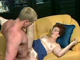 Old granny and muscular stud play love game on sofa